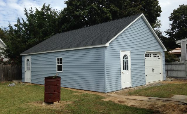 large blue one car garage and storage shed